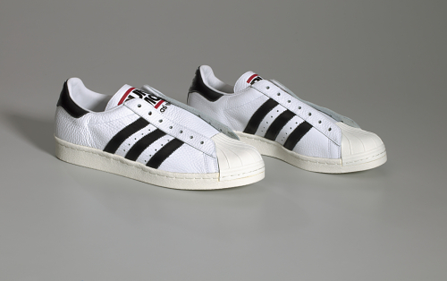A pair of white Run-D.M.C. Adidas shoes (.1ab), a pair of black fat shoelaces (.2ab), a pair of white shoelaces (.3ab), and the original shoebox with lid (.4ab).