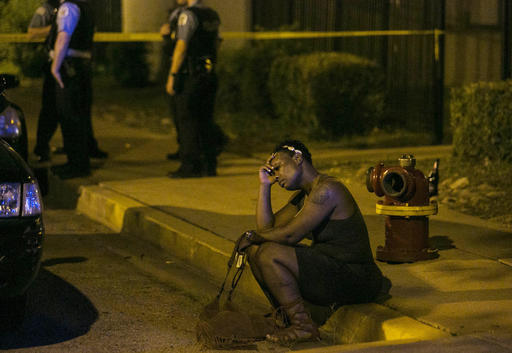 In this Aug. 7, 2016, photo, a woman sits on the curb as police in the background investigate the scene where gunfire at a birthday party left a man dead and a woman injured. The city's police department said Thursday, Sept. 1, 2016, Chicago recorded 90 homicides in August, its highest monthly death toll in two decades. (Ashlee Rezin /Chicago Sun-Times via AP)