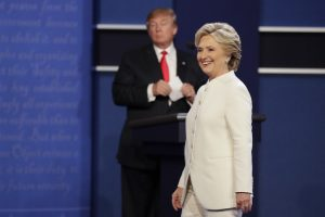 Democratic presidential nominee Hillary Clinton walks toward the audience as Republican presidential nominee Donald Trump stands behind his podium after the third presidential debate at UNLV in Las Vegas, Wednesday, Oct. 19, 2016. (AP Photo/John Locher)