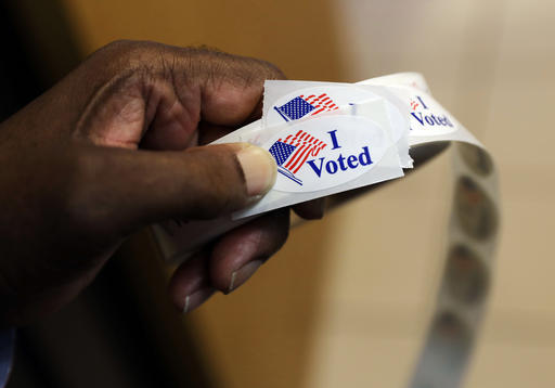 A volunteer prepares to hand out stickers to voters at an early polling station in Towson, Md., Tuesday, Nov. 1, 2016. In all, more than 45 million Americans are expected to vote before Election Day — or as much as 40 percent of all votes cast. (AP Photo/Patrick Semansky)