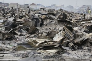 Residents salvage objects from the demolished houses that were set ablaze by government officials in Lekki, Lagos, Nigeria. Saturday, Nov. 12, 2016, Amnesty International says as many as 30,000 people in Nigeria's commercial capital are homeless after their community was set ablaze and demolished this week. (AP Photo/Sunday Alamba)