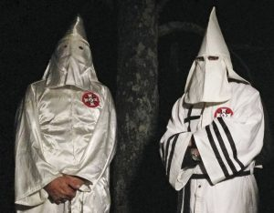 "In this Friday, Dec. 2, 2016 photo, two masked Ku Klux Klansmen stand on a muddy dirt road during an interview near Pelham, N.C. The KKK and other white extremist groups don't like being called ""white supremacists,"" a phrase that dates to the earliest days of white racist movements in the United States. (AP Photo/Jay Reeves)"