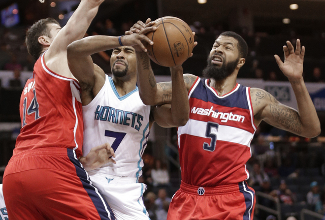 Charlotte Hornets' Ramon Sessions (7) is fouled as he drives between Washington Wizards' Markieff Morris (5) and Jason Smith (14) in the first half of an NBA basketball game in Charlotte, N.C., Monday, Jan. 23, 2017. (AP Photo/Chuck Burton)