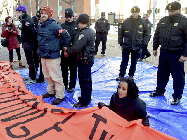 John Lugo, of Unidad Latina en Accion of New Haven, is arrested during a demonstration after some protesters blocked the intersection of Elm and College Streets in New Haven, Conn., Friday, Feb. 10, 2017, and refused to move. The protesters are in favor of changing the name of Yale University's Calhoun College. The peaceful arrests were pre-planned and coordinated between the demonstrators and New Haven Police. (Peter Hvizdak/New Haven Register via AP)