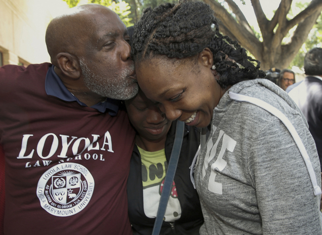 Andrew Wilson, left, kisses his granddaughter Souriya Hemphill, middle, and his daughter, Catrina Burks, as he leaves the Men's Central Jail in Los Angeles, Thursday, March 16, 2017. Wilson, whose murder conviction was tossed by a California judge is free after 32 years in prison. (AP Photo/Nick Ut)